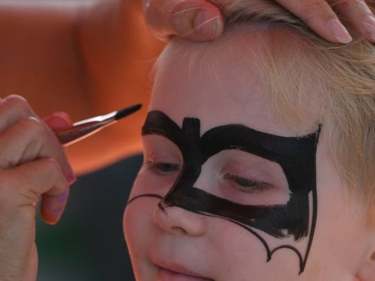 A young visitor takes advantage of face painting during