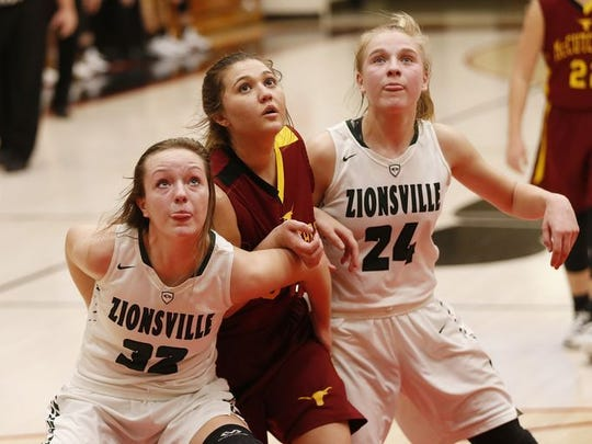 Zionsville's Maddie Nolan and Katey Richason block out McCutcheon's Halle Bares on Tuesday in girls basketball sectional action in Logansport.