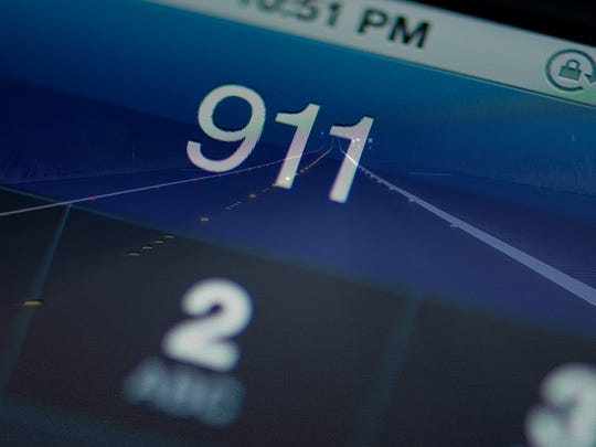 The phone number 911 appears on a phone screen over a dark road.