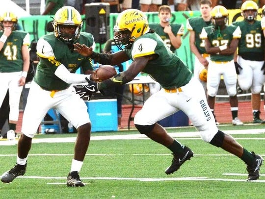 Captain Shreve quarterback Darrius Grant hands off