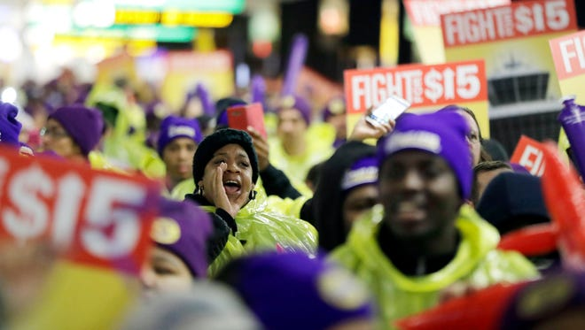 A woman shouts while marching with service workers asking for $15 minimum wage pay during a rally at Newark Liberty International Airport, Tuesday, Nov. 29, 2016, in Newark, N.J. The event was part of the National Day of Action to Fight for $15. The campaign seeks higher hourly wages, including for workers at fast-food restaurants and airports. (AP Photo/Julio Cortez)