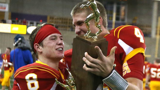 Carroll Kuemper seniors Cole Neary, right, and Cooper Kanne, hold the championship trophy after a win against Waukon in the Class 2-A title game.