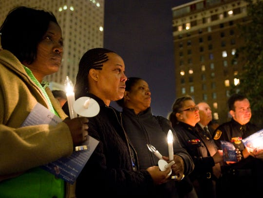 Memphis police officers including Donna Bowkin, (from left) Chartell Nelson and Trina Johnson listen to one of many speakers, including Memphis Mayor A C Wharton and MPD Director Toney Armstrong, during a candle light vigil in the Memphis City Hall plaza in honor of Officer Martoiya Lang on Dec. 19, 2012.