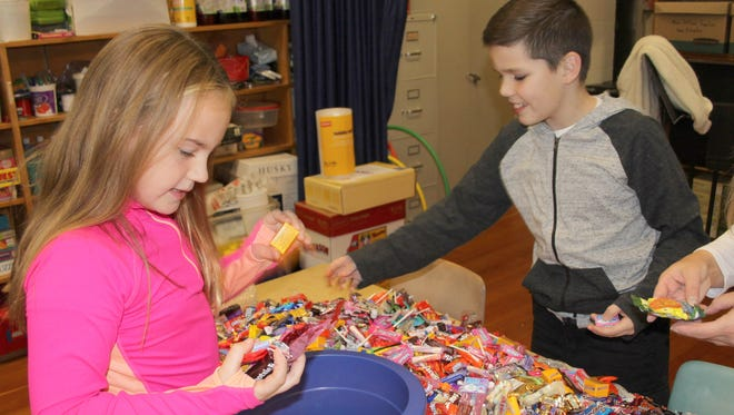 Lily Patelunas and Connor Carpenter, Gardner Road Elementary School third grade students, sort through donated candy during the school's recent Treats for Troops campaign.