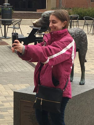 UMBC graduate Jen Wachtel takes a selfie with the statue of True Grit, the Chesapeake Bay Retriever mascot on campus a day after the men's basketball team pulled off the biggest upset in NCAA tournament history.