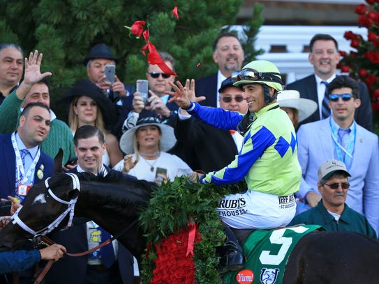 Jockey John Velazquez throws roses atop Always Dreaming