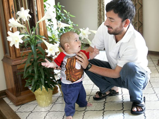 Qudrat strengthens his legs as he plays with his dad, Hakim, at the home of host and Rotary Club member Jim Graham's house in Brownsburg.