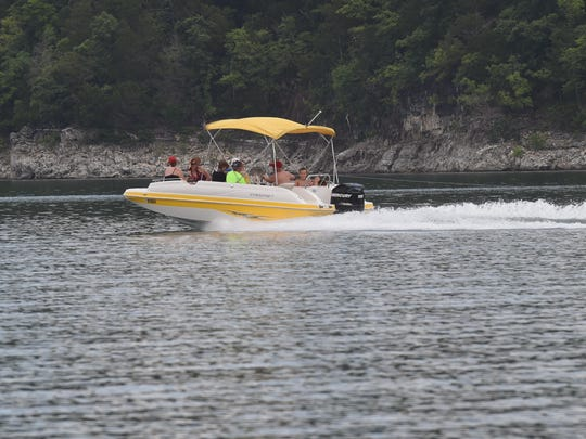 A boat with eight people in it tows a ninth person on Norfork Lake in this file photo. State law requires children 12 and under to wear life jackets when a boat is underway and that boaters have a life jacket for every person on the boat.