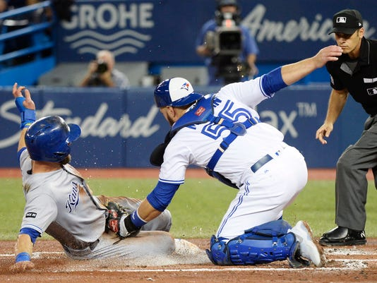 Kansas City Royals' Alex Gordon, left, slides home safely ahead of the tag by Toronto Blue Jays catcher Russell Martin (55) during the second inning of a baseball game in Toronto on Wednesday, Sept. 20, 2017. (Nathan Denette/The Canadian Press via AP)