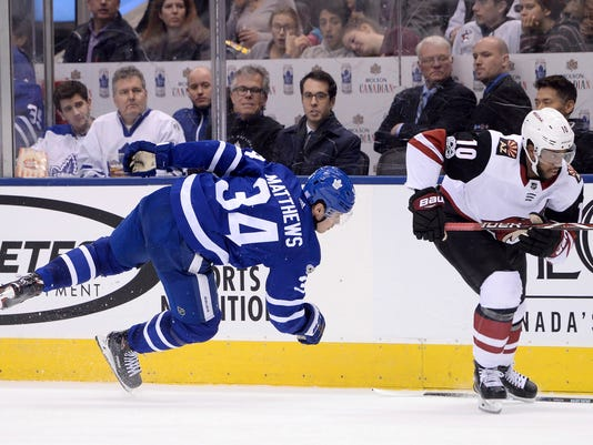 Toronto Maple Leafs center Auston Matthews (34) loses his stick as he's hit by Arizona Coyotes left wing Anthony Duclair (10) during third period NHL hockey action in Toronto on Monday, Nov. 20, 2017. (Nathan Denette/The Canadian Press via AP)