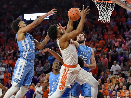 Clemson's Gabe DeVoe, center, grabs a rebound with seconds left on the clock while defended by North Carolina's Joel Berry II, left, and Luke Maye during the second half of an NCAA college basketball game Tuesday, Jan. 30, 2018, in Clemson, S.C. Clemson won 82-78. (AP Photo/Richard Shiro)