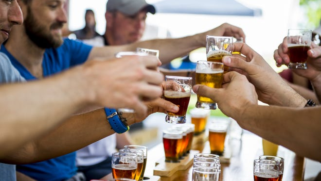 Guests drink samples from a flight of beers during a tour of Bayou Teche Brewing.