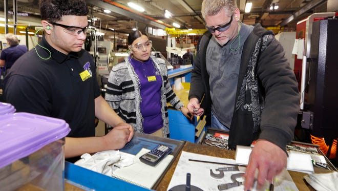 Miles Miller (right) a tool-and-die maker for Harley-Davidson, explains how parts are made to Bradley Tech students Ethan Sanchez and Debora Oquendo during a tour of the Harley-Davidson Powertrain Operations facility in Menomonee Falls.