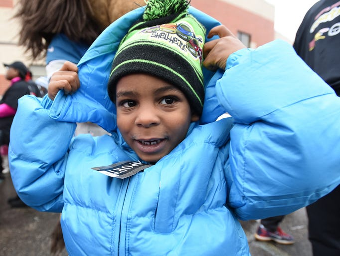 Dionte Carswell Jr., 4, from Detroit pulls up the hood