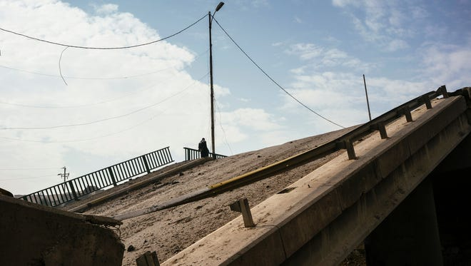 TOPSHOT - An Iraqi man stands on a bridge on January 21, 2017 which was destroyed by Islamic State (IS) group fighters in Mosul's al-Sukkar neighborhood, during the ongoing military operation against the jihadists. Iraqi forces battled the last holdout jihadists in east Mosul after commanders declared victory there and quickly set their sights on the city's west, where more tough fighting awaits. / AFP PHOTO / Dimitar DILKOFFDIMITAR DILKOFF/AFP/Getty Images ORIG FILE ID: AFP_KH03W