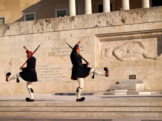 In this Dec. 10, 2016 photo, members of the Evzoni presidential guard perform the changing of the guard ceremony in front of the tomb of the unknown soldier at Syntagma Square in Athens. For travelers with more than beaches on their minds, there's plenty of upside to a brief winter visit to Athens that avoids the crowds and heat of summer.