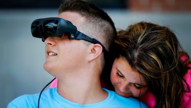 Maggie Miracle hugs her son Evan as he tries out a state-of-the-art device called eSight to restore his vision to 20/20. Miracle, who is legally blind, would be only the fifth person in Kentucky to receive the $15,000 unit.  