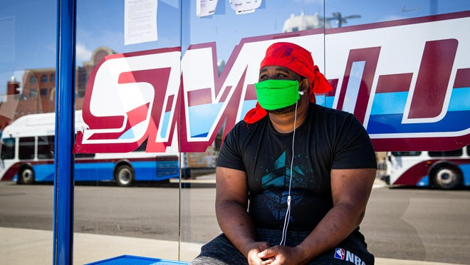 Keithen Gardner wears a homemade mask that was provided to him by SMTD as he waits for his bus at the SMTD Transfer Station on Adams Street, Wednesday, April 15, 2020, the first day that SMTD required customers to wear a face-covering of some sort.