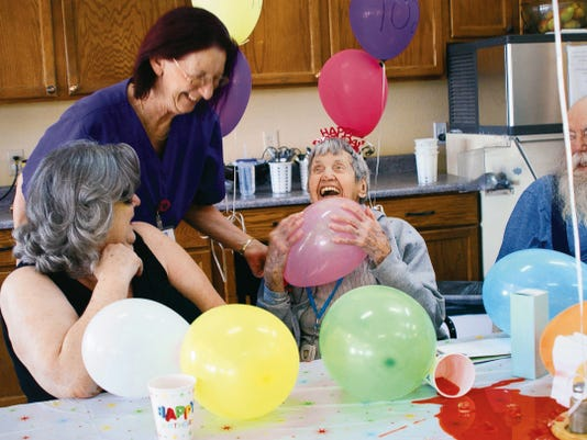 Ethel Root clutches a balloon during her 102nd birthday party celebrated last Friday at the Willow Manor Assisted Living Home in Deming. Flanking Ethel are Lucy and Bob Root, her son and daughter-in-law. Standing is Willow Manor caregiver Beverly Fiorentino.