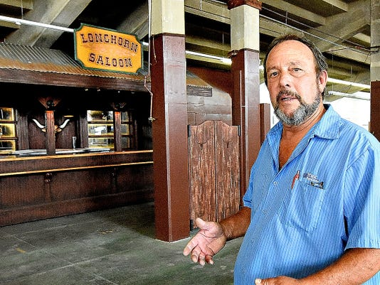 The York Fair's Michael Stauffer says it took him about a month and a half to build the Longhorn Saloon, a new western-themed bar under the grandstand for the York Fair. Stauffer built the structure by referencing a picture made by designer Ray Oweiler. At right, York Fair general manager Michael Froehlich shows off the player piano in the saloon.