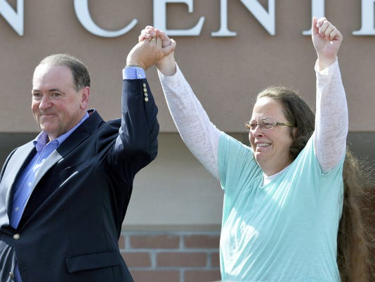 FILE - In this Tuesday, Sept. 8, 2015, file photo, Rowan County Clerk Kim Davis, with Republican presidential candidate Mike Huckabee at her side, greets the crowd after being released from the Carter County Detention Center, in Grayson, Ky. Politicians who may have thought they wouldn't have to say much at all about gay marriage once the U.S. Supreme Court effectively legalized it are being called on to say whether they support Davis.  (AP Photo/Timothy D. Easley, File)