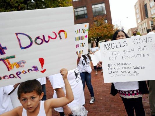 Ricky Dykes, 6, left, and Olga Davis, both of York, holds signs towards drivers on West Market Street during the Tired of the Violence rally on Continental Square in York Friday. York residents held anti-violence signs on the square before walking down West Market Street.