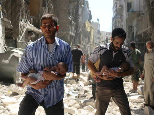 Syrian men carrying babies make their way through the