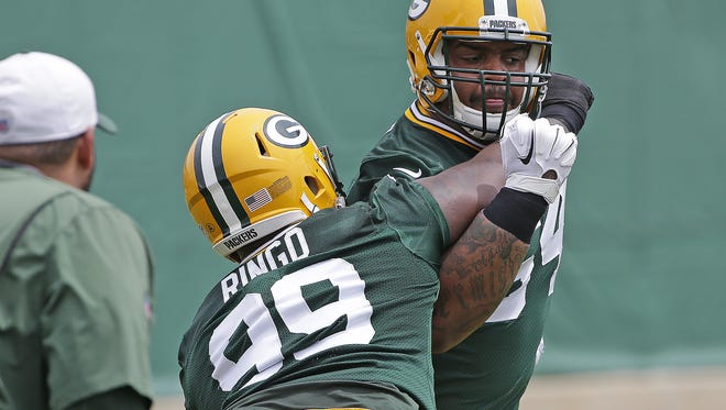 Green Bay Packers defensive tackle Mike Pennel (64) drills with Christian Ringo (99) during Organized Team Activities at Ray Nitschke Field on Tuesday.