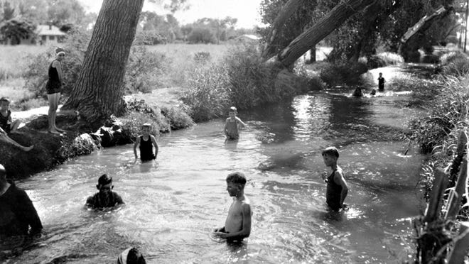 Canals, the lifeblood of the Valley, were the place to cool off, as seen in this 1920s photograph during Arizona's sweltering summers.