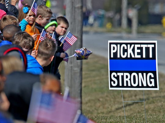 Students wave American flags as they watch the funeral procession of Boone County Deputy Jacob Pickett pass the White Lick Elementary School in Brownsburg, Friday, March 9, 2018.