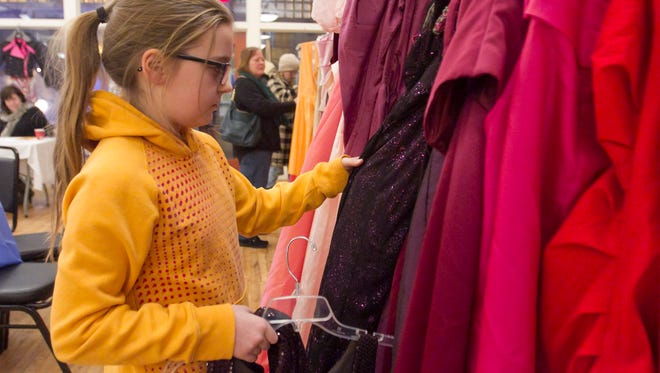 10-year-old Novi resident Elle Miller picks out dresses to be the raw material for her own Runway Repurposed creation as her grandmother Theresa Campbell of New Hudson and her mother Heather Campbell look for their own to use in the upcoming fashion show.