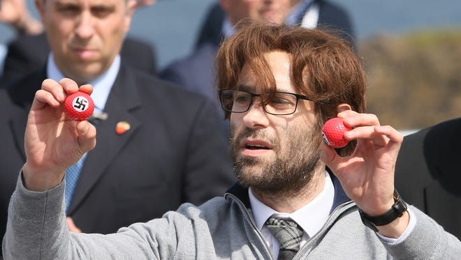 Security guards move June 24, 2016, to take away comedian Lee Nelson as he presents golf balls stamped with swastikas to protest presumptive GOP presidential nominee Donald Trump, in Ayr, Scotland, to officially open his Trump Turnberry Resort.