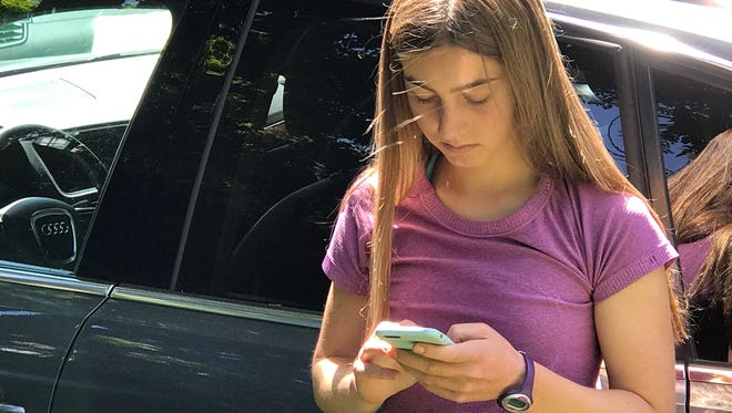 16-year-old Jeneva Toolajian, daughter of columnist Jennifer Jolly, texts on her iPhone in Oakland. CA.