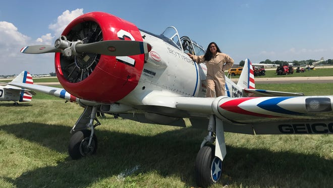 USA TODAY NETWORK-Wisconsin reporter Devi Shastri stands on the wing of a GEICO Skytyper plane.