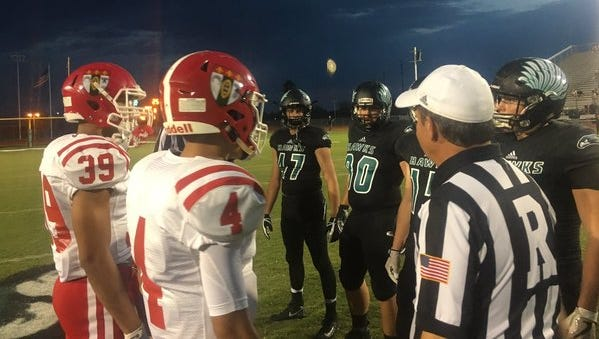 The captains for the Brophy College Prep Broncos and Highland Hawks meet near mid-field before their game on September 8, 2017.