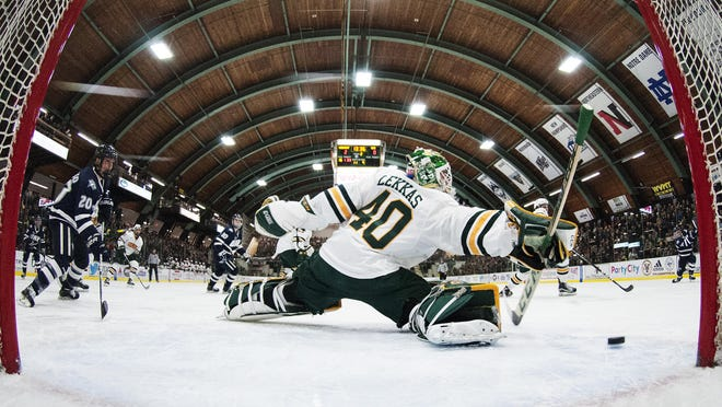 Catamounts goalie Stefanos Lekkas (40) tries to make a save during the men's hockey game between the New Hampshire Wildcats and the Vermont Catamounts at Gutterson Fieldhouse on Friday nighT.
