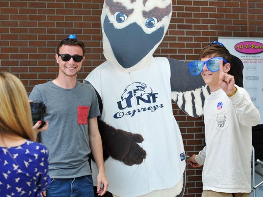 University of North Florida students have their picture taken with a cardboard cutout of Ozzie, the Ospreys mascot, on March 10.