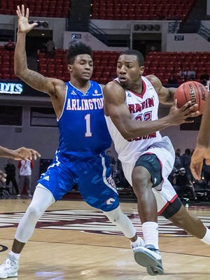 UL guard Johnathan Stove (22) drives to the basketbal against UTA Mavericks guard Erick Neal (1) during the Cajuns' 90-75 win Saturday in the Cajundome.