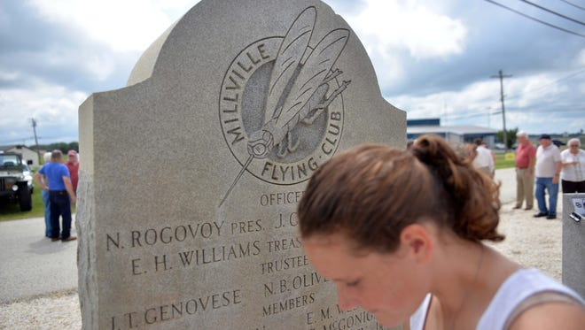 Millville High School sophomore Kayla Piper, 16, walks past the 1941 monument commemorating the dedication of Millville Airport, Tuesday, Aug. 2, 2016 in Millville.