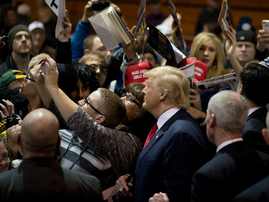 Donald Trump takes a selfie with supporters at a rally