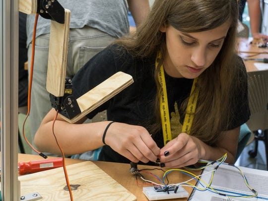 Kate Magnuson works to assemble a robotic arm that reads cues from muscle sensors attached to a human arm during Robotics 101 camp in July.