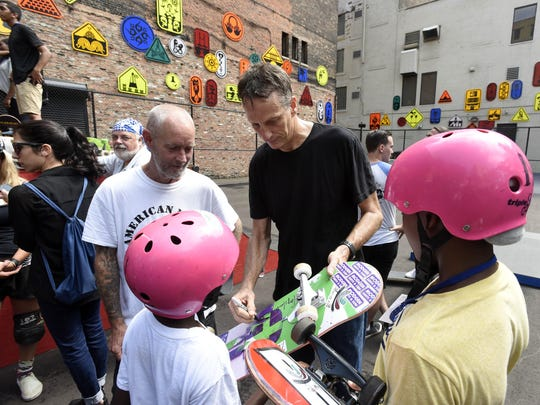 Tony Hawk, center, signs an autographs for Rashad Wright, foreground, left, and his cousin, Daishon Nelson, both 11 and of Detroit, as Hawk stands with fellow pro-skater Bill Danforth, left.