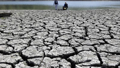 Cracks appear in the dry bed of the Stevens Creek Reservoir in Cupertino, Calif., in March. A study has asserted a link between climate change and the intensifying California drought.