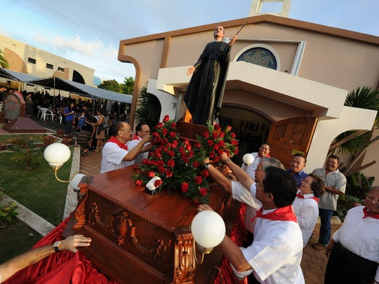 In this file photo, ushers prepare to return the statue of their patron saint, Diego Luis de San Vitores, back to the church after a procession was held in Tumon on Jan. 14 2012.
