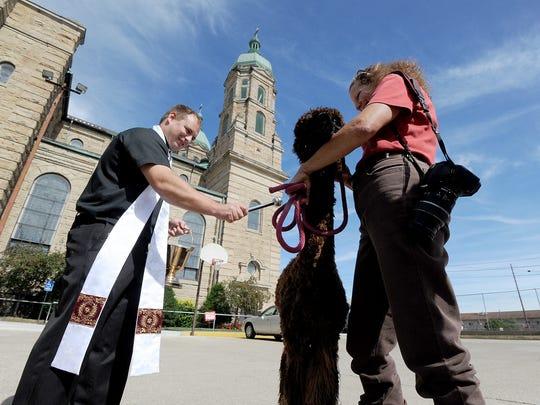 Fr. Jeremy Miller of St. Peter's Catholic Church sprinkles