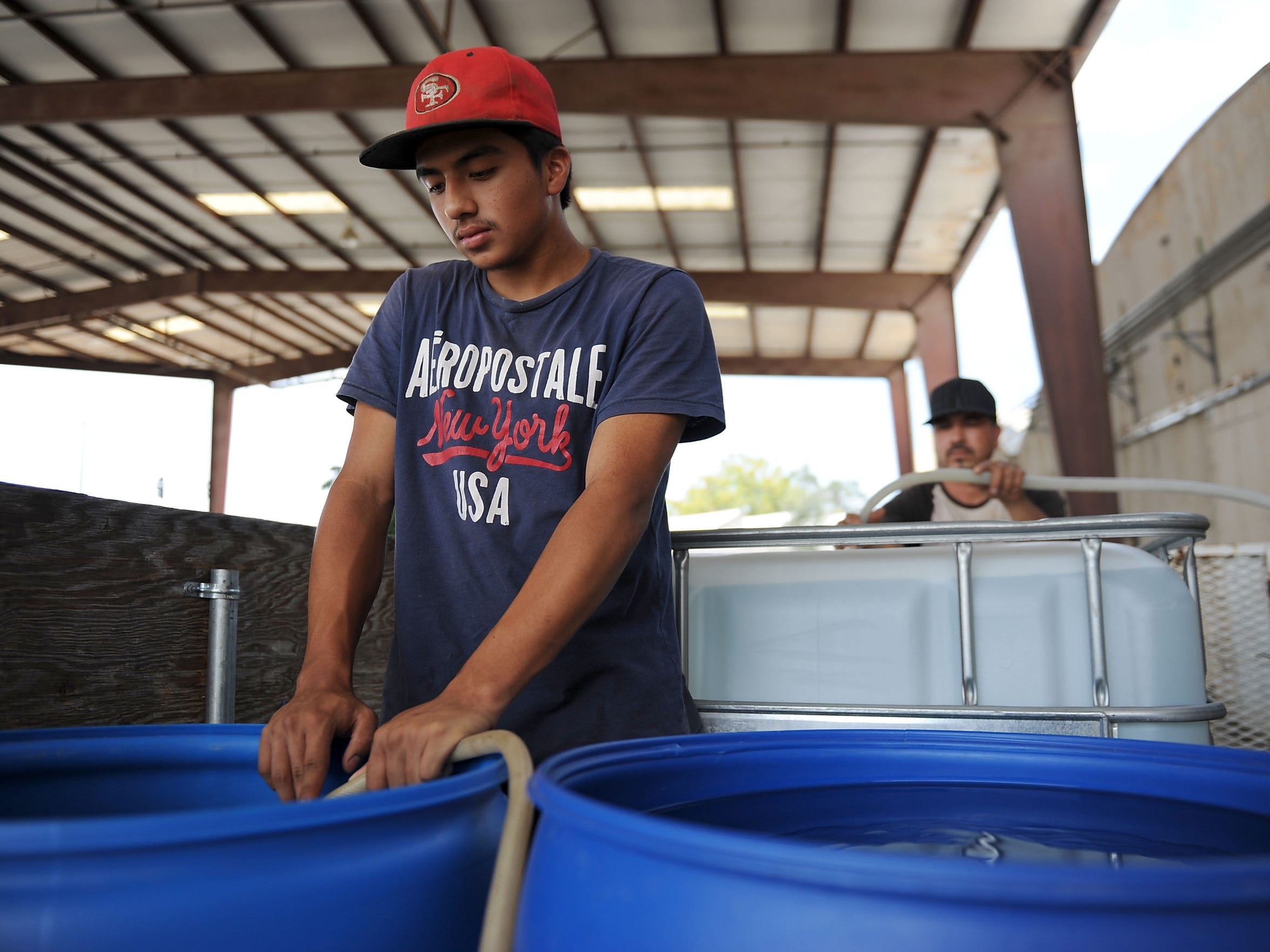 Diego Bedolla fills a plastic barrel with a hose at