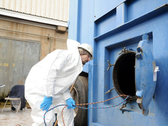 An environmental services worker examines an oil tank