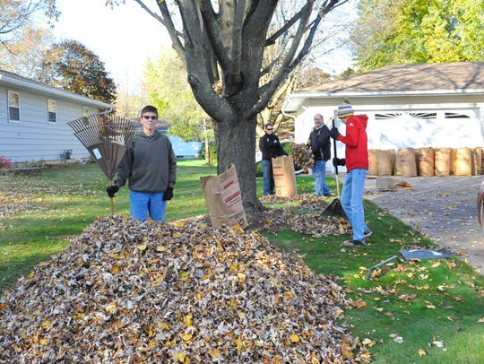 Kyle Grossman shows off a large pile of leaves he and
