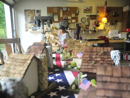 Dave Woodruff works in his garage next to a display