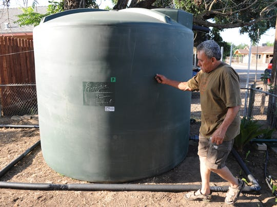 Farmworker Enrique Olivera taps on a newly delivered water tank at his home near Visalia, California, in 2015. He and his wife, Yolanda Galvan, received the tank through a program in Tulare County that assists low-income families whose wells have gone dry.